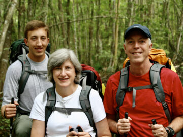 two men and a woman with hiking gear