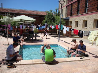people soaking their feet in a pool at an albergue