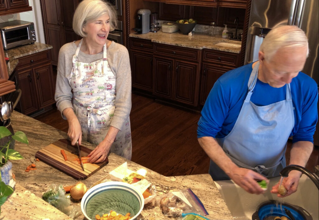 Helen and Wick in the kitchen with carrots for the Camino Chicken Vegetable Soup