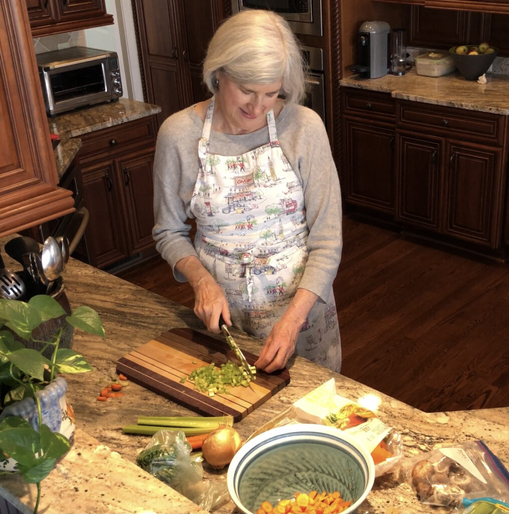 Helen wearing an apron chopping celery for this simple chicken vegetable soup