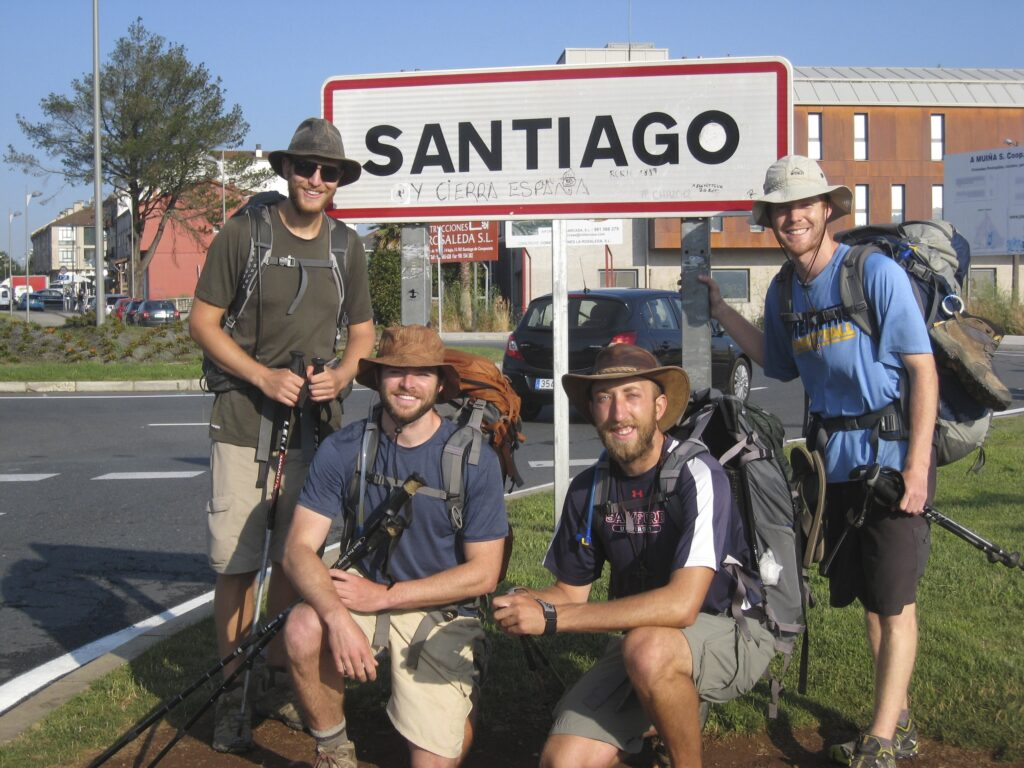 Four Camino pilgrims with Santiago ton sign