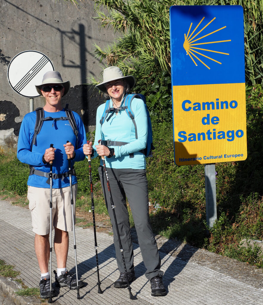 Helen and Wick in hiking clothes standing by a road sign for the Camino de Santiago