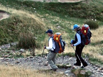 Helen and Wick in hiking clothes and backpacks going down a hill