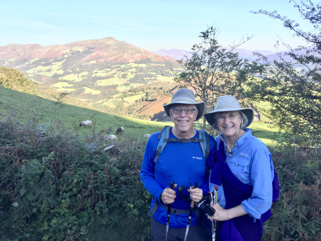 Helen and Wick in hiking clothes on the Camino Frances with Pyrenees mountains