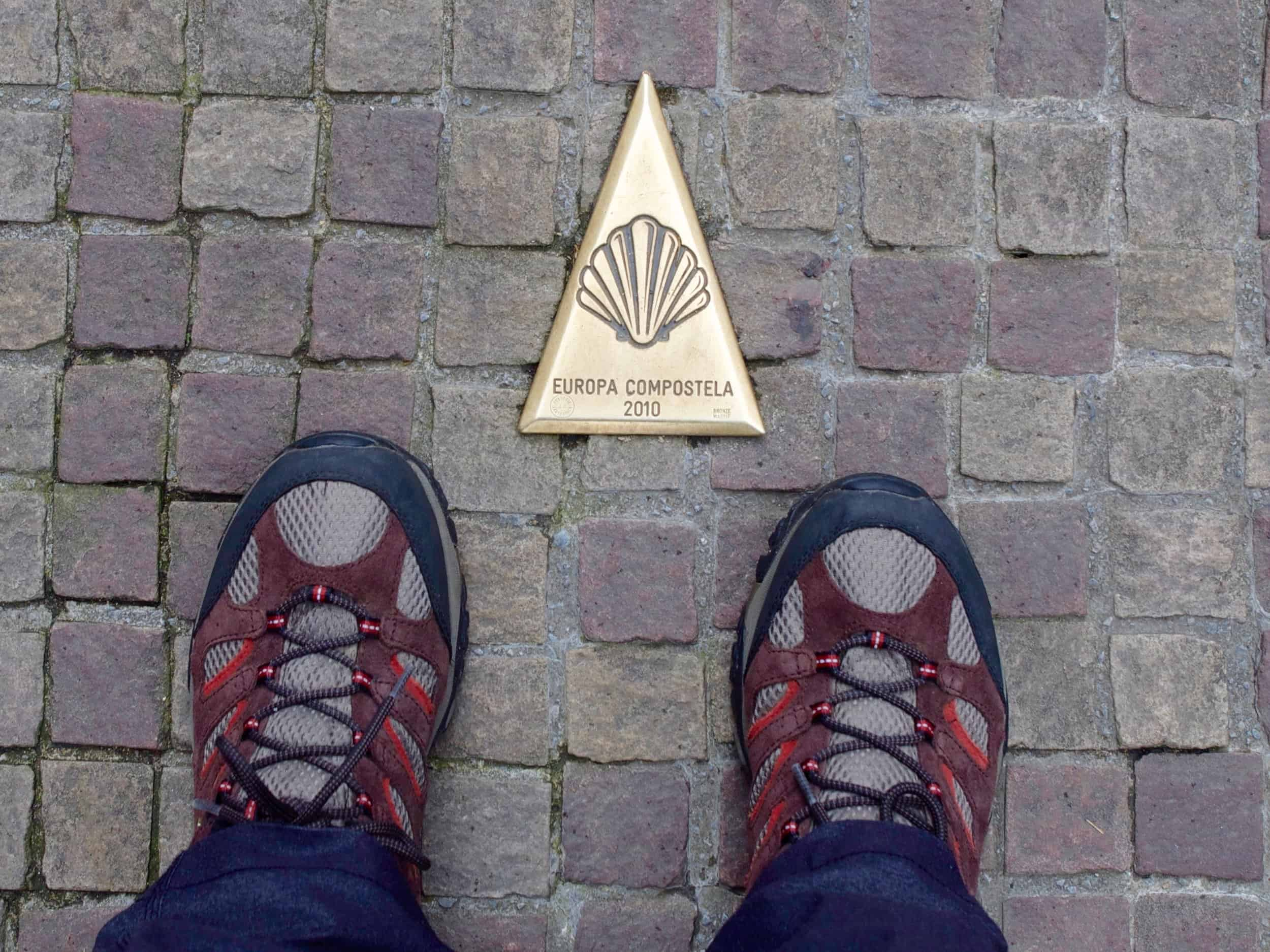Merrell Moab hiking shoes standing near a brass plaque on the Camino de Santiago road