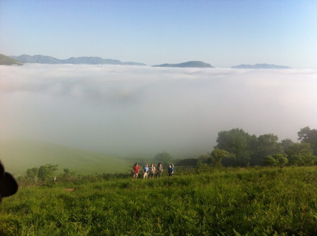 Hunter and his friends crossing the Pyrenees with low clouds behind them on their way to the Hill of Forgiveness
