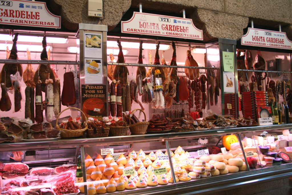 Hams, sausages, and other meats hanging on display above a counter with local cheeses at the Mercado de Abastos