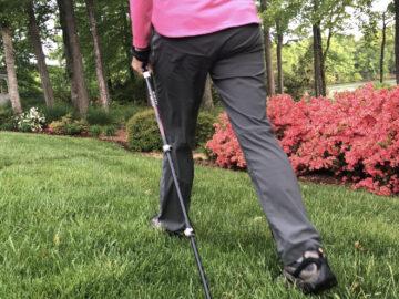 Start walking now walker's legs and walking poles going by pink azaleas