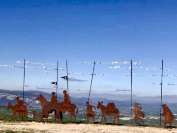 metal pilgrim procession sculture on the Hill of Forgiveness in Spain with bright blue sky