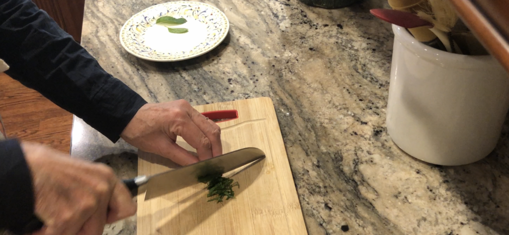 hands holding knife chopping fresh mint on a wooden cutting board