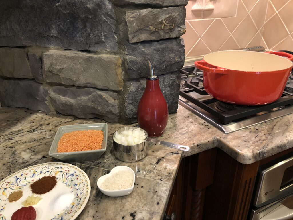 stove with orange soup pot and ingredients for the Red Lentil Soup Abastos